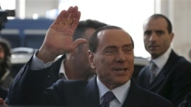 Former Italian Prime Minister Silvio Berlusconi arrives at the central train station, Milan, Dec. 29, 2012.