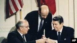 美國前總統裡根(右)與前蘇聯領導人戈爾巴喬夫1987年12月8日簽署《中導條約》後交換簽字筆(美聯社)