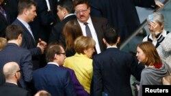 Kanselir Jerman Angela Merkel (berbaju kuning) bersama anggota Parlemen Jerman setelah memberikan suara mendukung perpanjangan 4 bulan program dana talangan untuk Yunani (27/2).