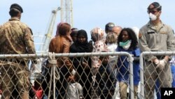 FILE - Migrants wait to disembark an Italian Navy ship in the port of Palermo, Sicily, southern Italy, May 2, 2014.