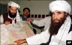 FILE - Sirajuddin Haqqani, far left, and Jalaluddin Haqqani, far right, then Taliban Army Supreme Commander, meet with reporters in Miram Shah, Waziristan on Aug. 22, 1998.