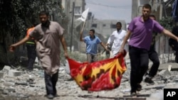 Palestinians, one holding a white flag, flee Gaza City's Shijaiyah neighborhood, northern Gaza Strip, July 20, 2014.