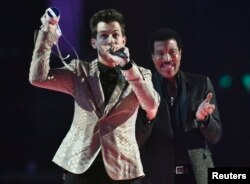 Mark Ronson celebrates with Lionel Richie after receiving the British Single award at the BRIT music awards at the O2 Arena in Greenwich, London, Feb. 25, 2015.