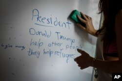 A volunteer teacher erases the board after teaching her Christian Burmese refugees English in Kuala Lumpur, Malaysia, March 11, 2017.