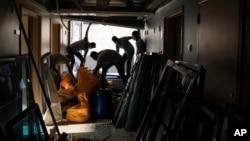 Workers remove debris from the Saint George Hospital, heavily damaged in last week's massive explosion in Beirut, Lebanon, Thursday, Aug. 13, 2020. (AP Photo/Felipe Dana)
