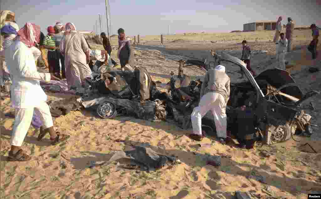 People check the scene where a car bomb exploded in near the port town of El-Arish in Egypt's Sinai peninsula, July 24, 2013.