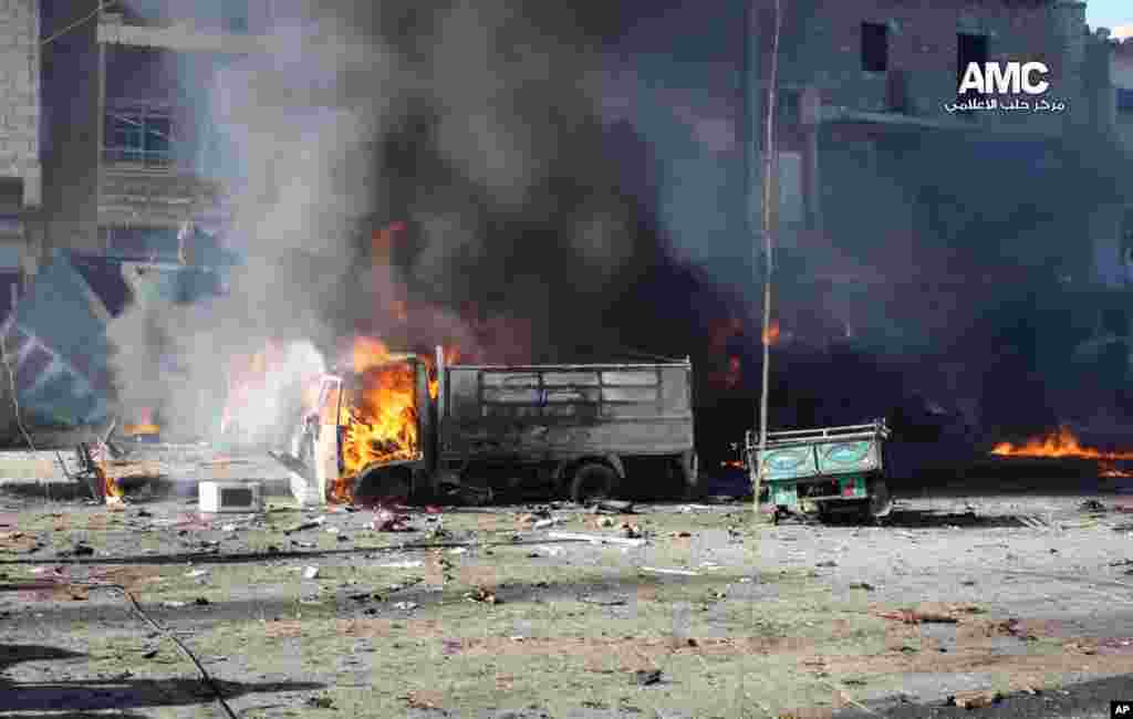 In this citizen journalism image, vehicles burn after a Syrian aircraft pummeled an opposition neighborhood in Aleppo, Syria, Dec. 22, 2013.
