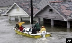 FILE - St. Berard Parish deputy sheriff Jerry Reyes uses his boat to rescue residents after Hurricane Katrina hit the area causing flooding in their New Orleans neighborhood, Aug. 29, 2005.