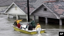 FILE - St. Bernard Parish Deputy Sheriff Jerry Reyes uses his boat to rescue residents after Hurricane Katrina hit the area causing flooding in their New Orleans neighborhood, Aug. 29, 2005.