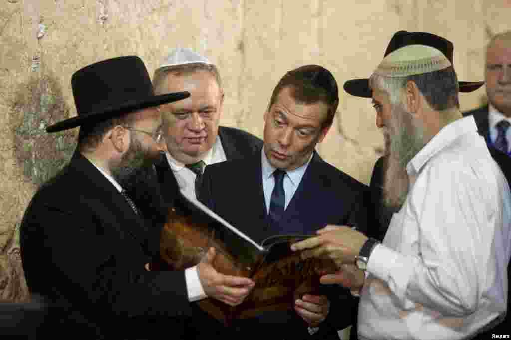 នាយករដ្ឋមន្រ្តីរុស្ស៊ីលោក Dmitry Medvedev (កណ្តាល) មើលទៅសៀវភៅមួយក្បាល ដែលត្រូវបានបង្ហាញដល់លោកអំឡុងពេលទស្សនកិច្ចនៅជញ្ជាំង Western Wall ក្នុងរដ្ឋធានីហ្សេរ៊ុយសាឡិម។