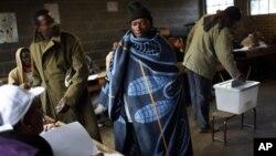 Seorang warga Lesotho menggunakan selimut tradisional bersiap untuk memberikan suaranya di TPS Sekolah Mpho, Maseru, Lesotjo (26/5).