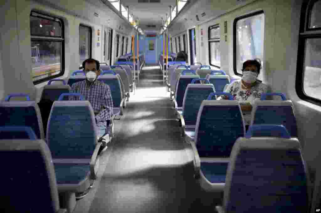 People wearing masks as a measure to protect against the spread of the new coronavirus ride a nearly empty train in Buenos Aires, Argentina.