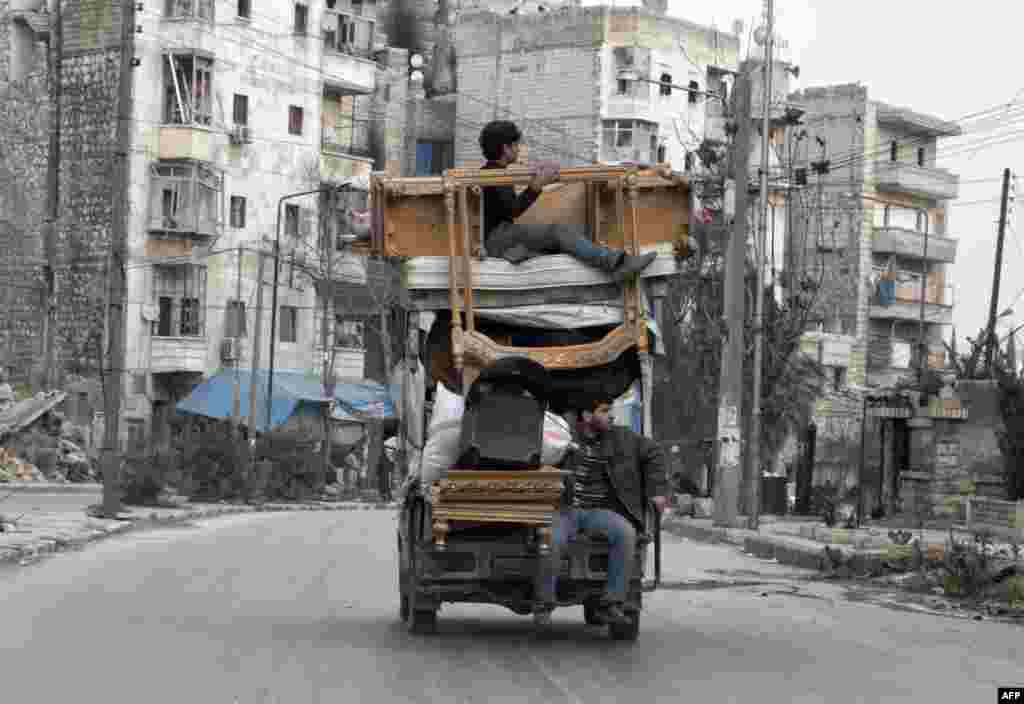 Syrians transport their belongings from one neighbourhood to another in the northern Syrian city of Aleppo on January 27, 2015. The ancient city of Aleppo has been fought over mercilessly since a popular uprising against President Bashar al-Assad began in