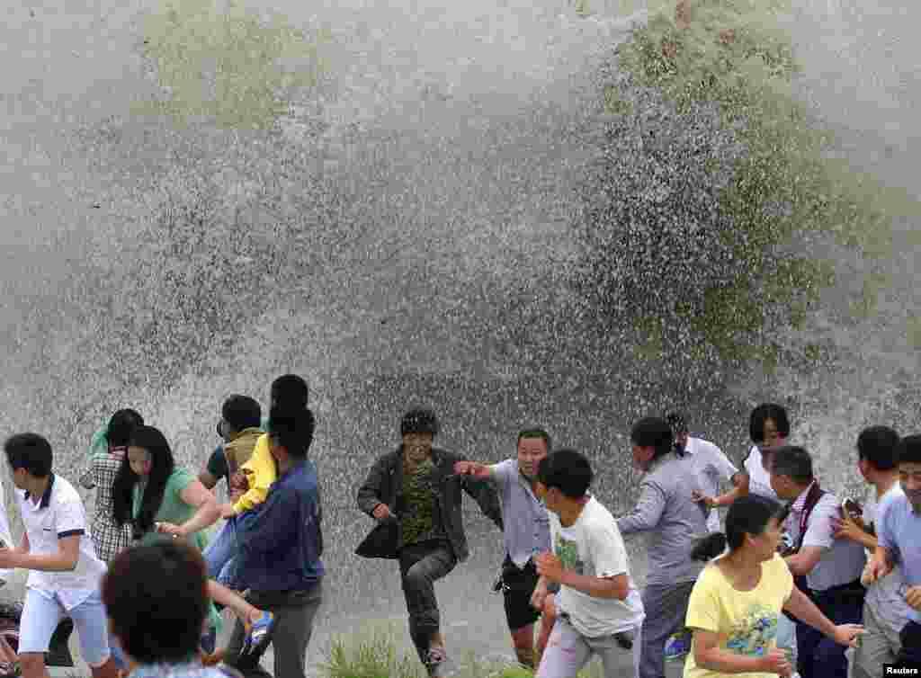 Warga lari menghindari ombak yang menabrak pembatas di sungai Qiantang, di Hangzhou, Zhejiang, China.