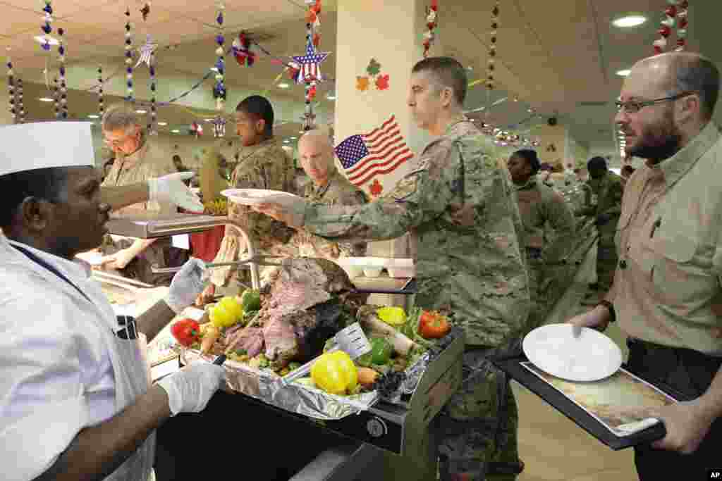 A dining facility worker, left, serves soldiers and civilians for their Thanksgiving meal at the U.S.-led coalition base in Kabul, Afghanistan, November 22, 2012.