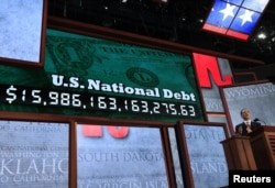 FILE - Standing in front of a large U.S. national debt clock, Republican National Committee Chairman Reince Priebus addresses the 2012 Republican National Convention opening session in Tampa, Florida, August 27, 2012.