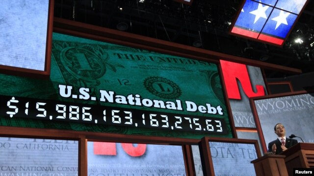 Republican National Committee Chairman Reince Priebus unveils a large U.S. national debt clock at the opening of the 2012 Republican National Convention in Tampa, Florida, August 27, 2012.