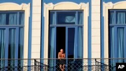 FILE - A tourist looks out from his hotel room's balcony in Havana, Cuba.