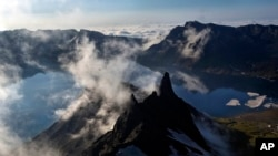 In this Wednesday, June 18, 2014 photo, clouds float over the peak of Mt. Paektu in North Korea's Ryanggang province. More than a thousand years ago, a huge volcano straddling the border between North Korea and China was the site of one of the biggest eruptions in history.