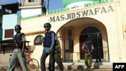Kenyan police officers stand guard outside the Masjid Swafaa mosque in the district of Kisauni in Kenya's coastal town of Mombasa following a raid, Nov. 19, 2014.