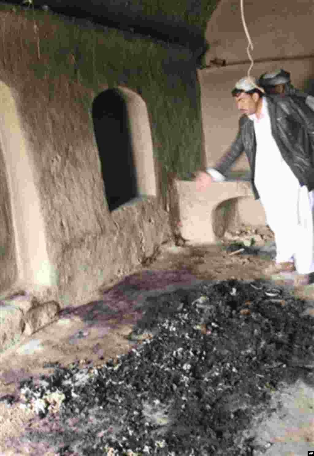 A man points to bloodstains, where witnesses say Afghans were killed by a U.S. service member, in Panjwai, Kandahar province south of Kabul, Afghanistan, Sunday, March 11, 2012. A U.S. service member walked out of a base in southern Afghanistan before daw