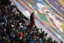 A Tibetan Buddhist monk stands between tourists and a giant thangka, a religious silk embroidery or painting unique to Tibet, during the Shoton Festival at Drepung Monastery on the outskirts of Lhasa, Tibet Autonomous Region, August 29, 2011.