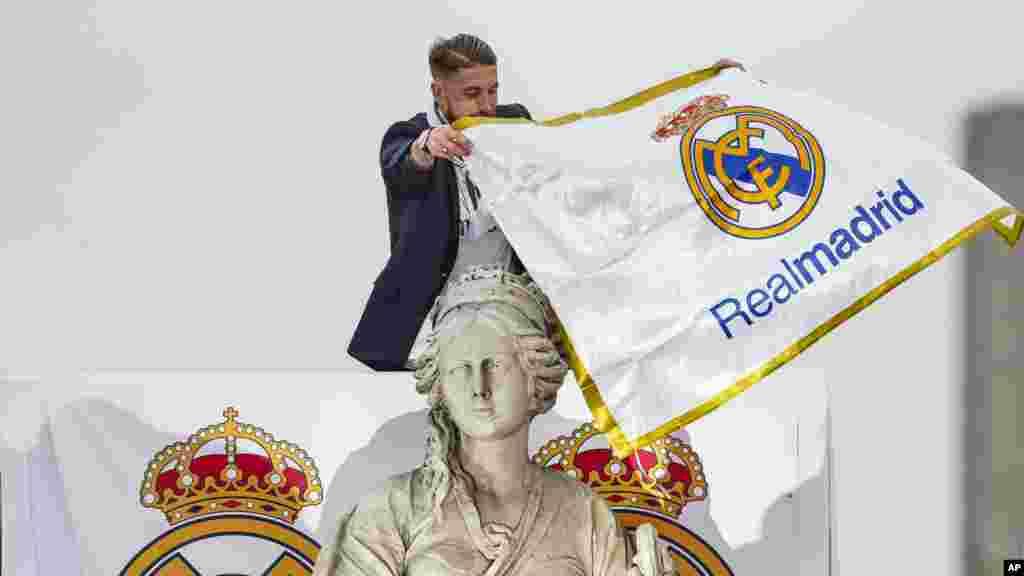 Le joueur du Real Madrid Sergio Ramos lie un drapeau de l'équipe autour du cou de la déesse Cibeles, lors du défilé dans les rues de Madrid, le 29 mai 2016.