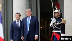 French President Emmanuel Macron greets U.S. President Donald Trump at the Elysee Palace in Paris, July 13, 2017.