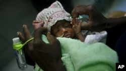 FILE - Three-day-old premature baby Jessica Thelusma is carried by her mother Silvie Estain in the emergency room at General Hospital in Port-au-Prince, Haiti.
