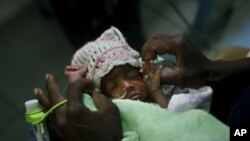 Three-day-old premature baby Jessica Thelusma is carried by her mother Silvie Estain in the emergency room at General Hospital in Port-au-Prince, Saturday, May 8, 2010. (AP Photo/Esteban Felix)