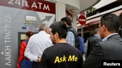 A man makes a transaction at an ATM outside a branch of Laiki Bank in Nicosia, March 21, 2013.