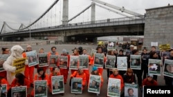 Greenpeace activists hold portraits of those detained on the boat Arctic Sunrise during a protest in Moscow, Russia, Oct. 5, 2013.