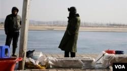 中國漁民在丹東的河邊賣魚,河對岸是朝鮮邊境城鎮新義州。(2013年2月7日)