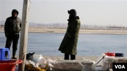 Ngư dân Trung Quốc bán cá trên bờ sông Đan Đông, đối diện với thị trấn biên giới Sinuiju của Bắc Triều Tiên.