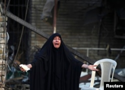 A woman reacts at the site of a car bomb attack, at the entrance to the neighbourhood of Kadhimiya in Baghdad, October 15, 2014. REUTERS/Ahmed Saad