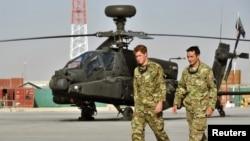 Pangeran Harry berjalan melewati helikopter Apache di Camp Bastion, Afghanistan 7 September 2012. (Foto: REUTER/John Stillwell/POOL)