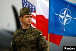 一名波蘭軍人站立在波蘭、美國和北約旗幟前。