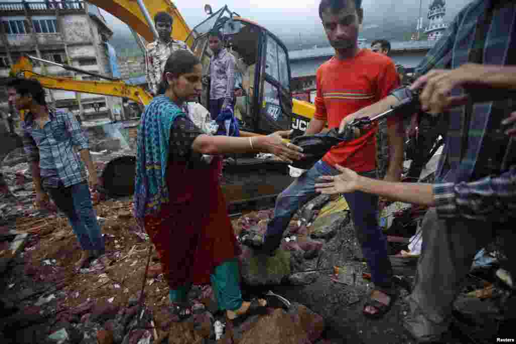 A resident receives help while carrying her possessions recovered from the rubble of a collapsed residential building on the outskirts of Mumbai, India, June 21, 2013.