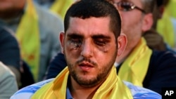 A Hezbollah fighter who was wounded in Qusair, Syria, listens to a speech by Hezbollah leader Sheik Hassan Nasrallah, not shown, during a rally in the southern suburb of Beirut, Lebanon, Friday, June 14, 2013.