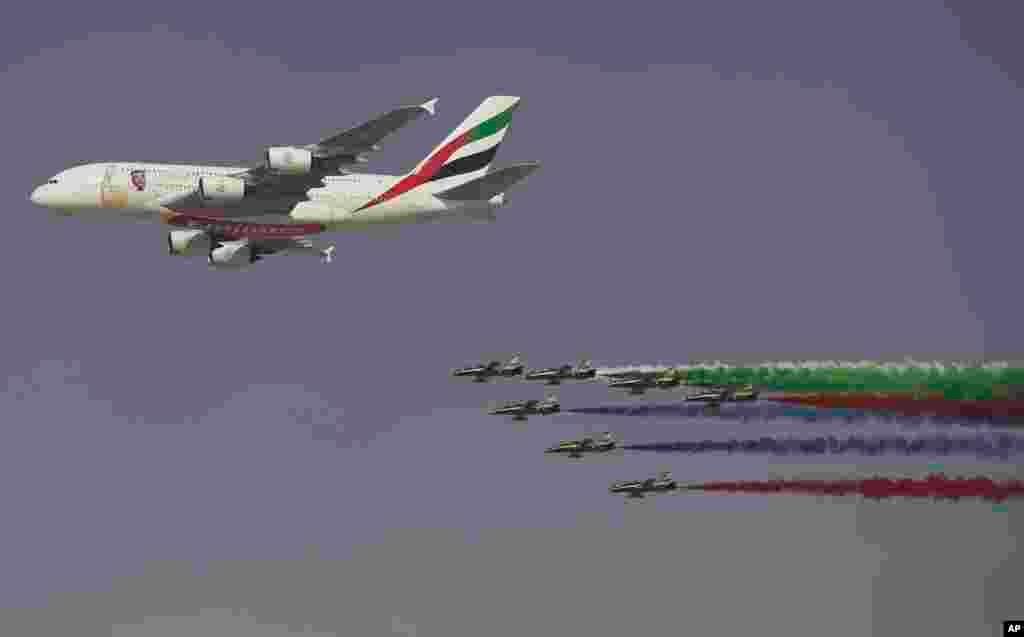 امارات ایئر لائن کا اے-380 اور اس کے پیچھے الفرسان نامی ایروبیٹک ٹیم فلائئ پاسٹ کا مظاہرہ کرتے ہوئے