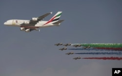 "An Emirates Airline A-380 leads the ""Al Fursan"", or the Knights, a UAE Air Force aerobatic display team, during the opening day of the Dubai Air Show, United Arab Emirates, Nov. 12, 2017."