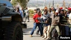 Para pekerja tambang yang mogok kerja memberi jalan bagi kendaraan petugas keamanan di pertambangan AngloGold Ashanti, Carletonville, Johannesburg, Afrika Selatan (Foto: dok). Dua pekerja tambang tertembak setelah mencoba menerobos gudang senjata milik Forbes Coal di propinsi KwaZulu-Natal, Afrika Selatan.