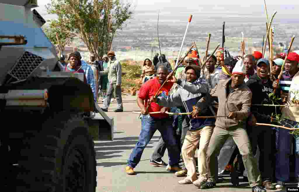 Striking miners react as they make way for a security vehicle at the AngloGold Ashanti mine in Carletonville, northwest of Johannesburg, South Africa, October 25, 2012.