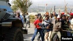 Kendaraan pasukan keamanan melewati sekelompok buruh tambang di Johannesburg, Afrika Selatan (25/10). Buruh tambang kembali melakukan aksi mogok di Afsel.