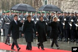 FILE - German Chancellor Angela Merkel, second left, welcomes the President of Egypt, Mohamed Morsi, second right, with military honors at the chancellery in Berlin, Germany, Wednesday, Jan. 30, 2013.