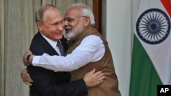 FILE - Indian Prime Minister Narendra Modi, right, hugs Russian President Vladimir Putin before their meeting in New Delhi, India, Oct. 5, 2018.