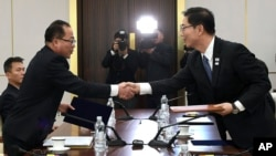 In this photo provided by South Korea, South Korean Vice Unification Minister Chun Hae-sung, right, shakes hands with the head of North Korean delegation Jon Jong Su during a meeting at Panmunjom in the border area between the two Koreas Jan. 17, 2018. (South Korea Unification Ministry via AP)