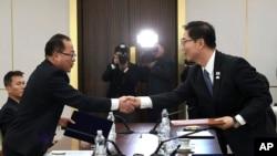 韩国统一部次长千海成(右)和朝鲜代表团团长田钟秀在韩国非军事区板门店举行会谈时握手.(2018年1月17日 韩国统一部提供)