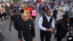 Hashim Nzinga, front left, a marcher who identified himself as national chairman of the New Black Panthers, marches with others in Charleston, to the Emanuel AME Church, six days after a gunman shot nine people inside the building, June 23, 2015.