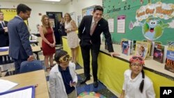 House Speaker Paul Ryan of Wis., right, and Rep. Carlos Curbelo, R-Fla., left, watch as students Christian Rubio, left foreground, and Jocelyn Zuniga, right foreground, explore the effect of friction on different surfaces, during a Science class at Caribbean Elementary School, Wednesday, Oct. 19, 2016, in Miami.